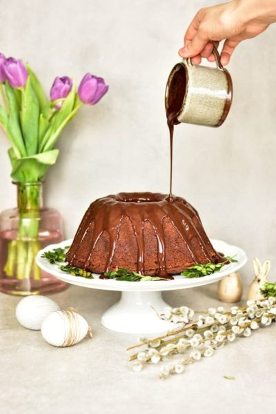 bundt cake with chocolate glaze being poured over it on a white cake stand