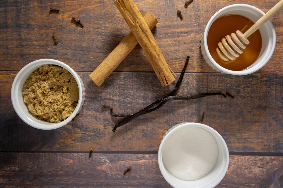 brown sugar, white sugar and honey in bowls surrounded by whole cloves and cinnamon sticks