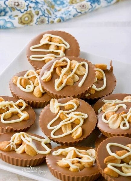 a pile of chocolate cups topped with peanuts and a white chocolate drizzle
