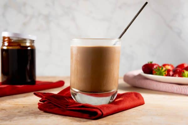 A glass of chocolate milk surrounded by strawberries and chocolate syrup