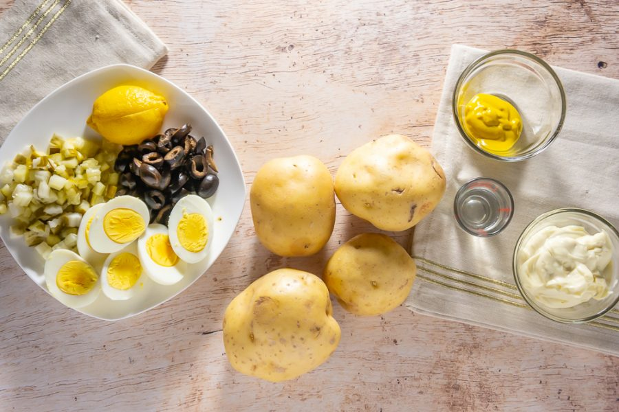 Potatoes next to a plate of olives, eggs, lemon, pickes, and mustard and mayo