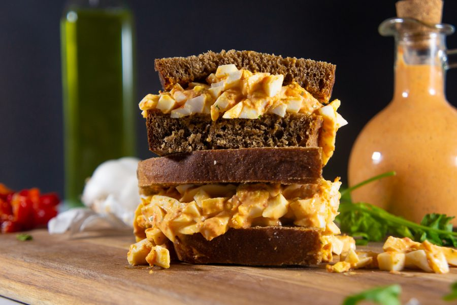 an egg salad sandwich made with red pepper aioli on a wooden cutting board