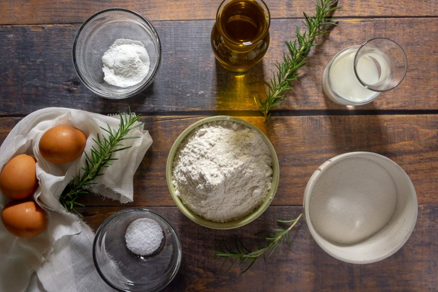 a collection of ingredients including flour, olive oil, eggs, sugar, rosemary and baking powder