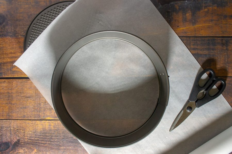 a springform pan with parchment paper and scissors