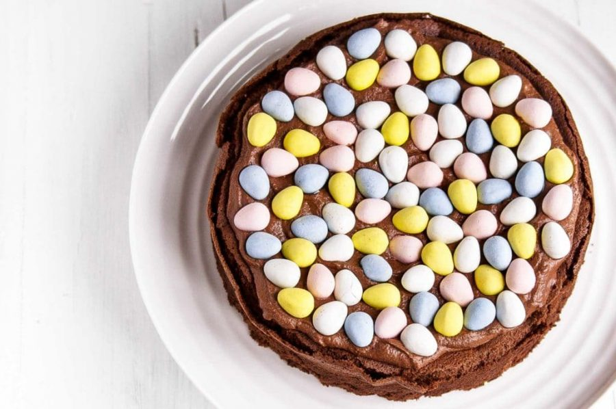 chocolate cake topped with chocolate cream and colored chocolate easter eggs