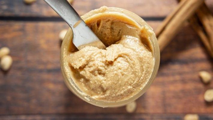 an overhead shot of a jar of homemade peanut butter