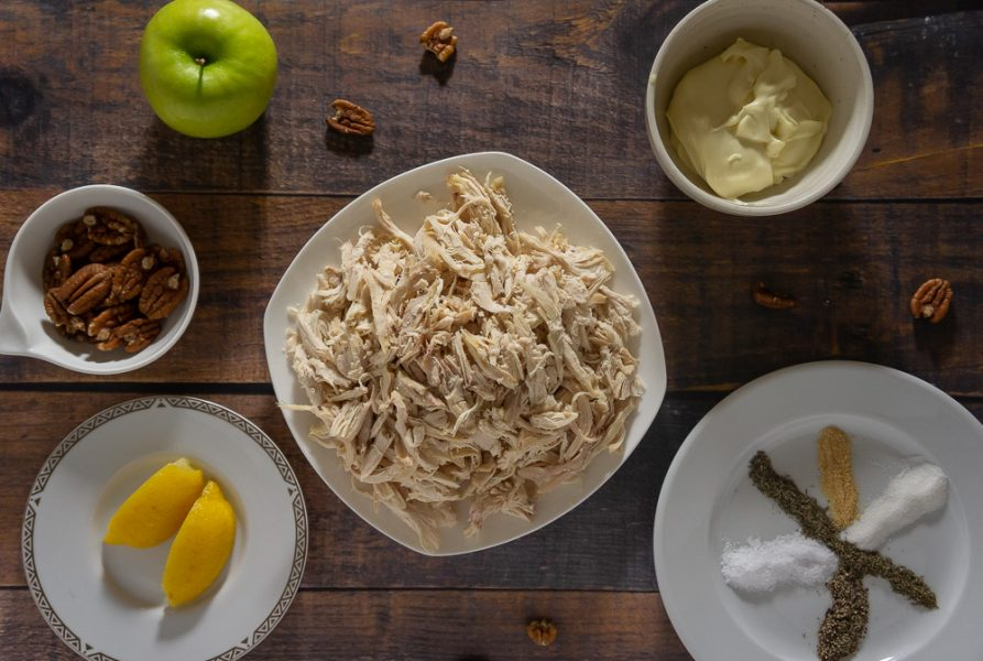 Shredded chicken, a green apple, lemon wedges, pecans, mayo and spices