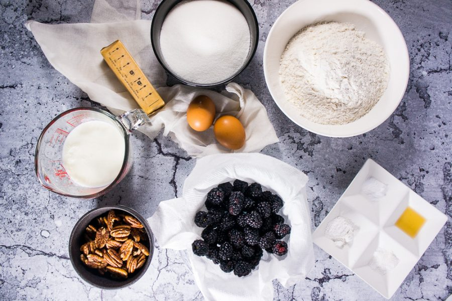 Blackberries, sugar, flour, buttermilk, eggs, butter, and pecans in different bowls.