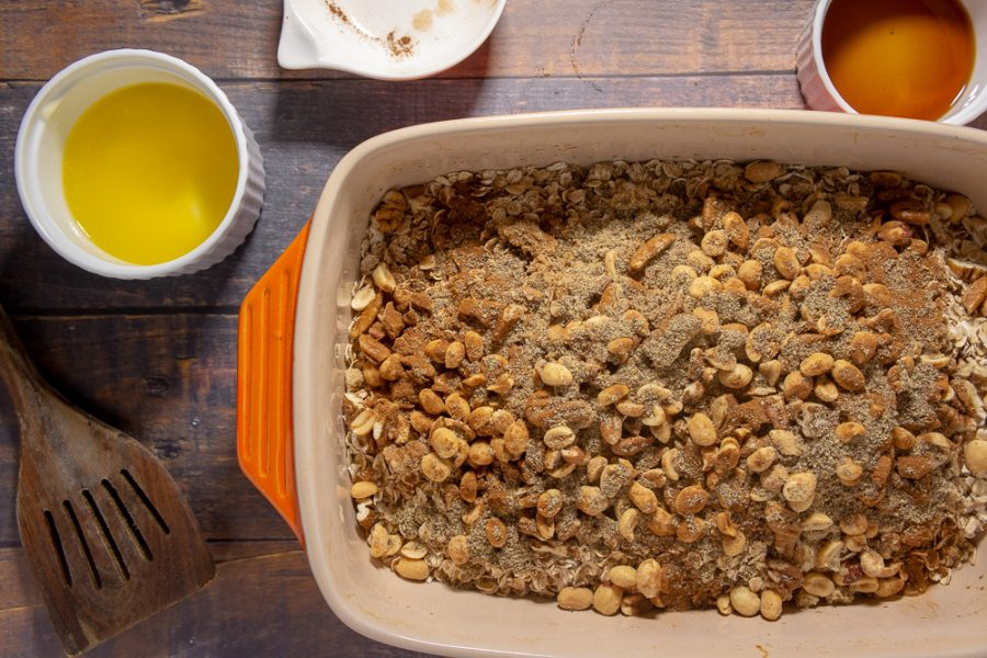 a 9x13 baking dish with oats and nuts topped with cinnamon, flax, and sugar.