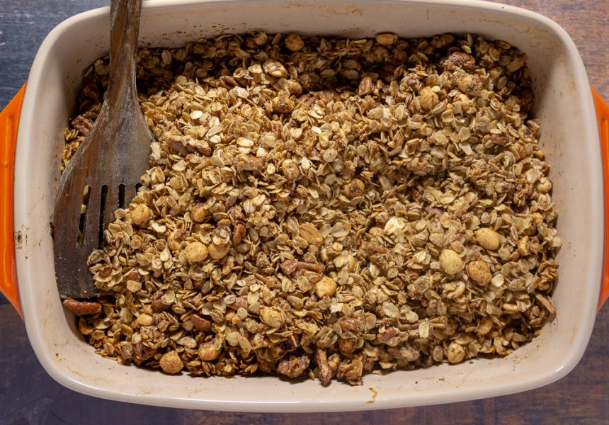 An orange casserole dish full of homemade granola with nuts.