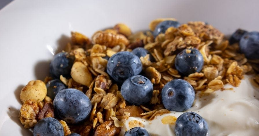 A bowl of homemade granola on yogurt with blueberries