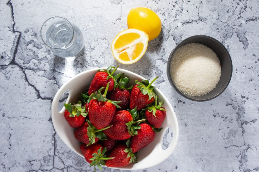 a bowl of strawberries, one lemon cut in half, a bowl of sugar, and water