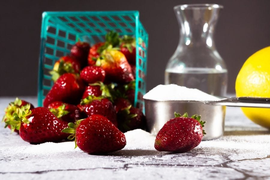 A pile of strawberries with a cup of sugar, water, and a lemon
