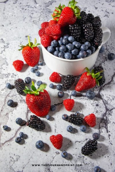 A white bowl with blueberries, raspberries, blackberries, and strawberries